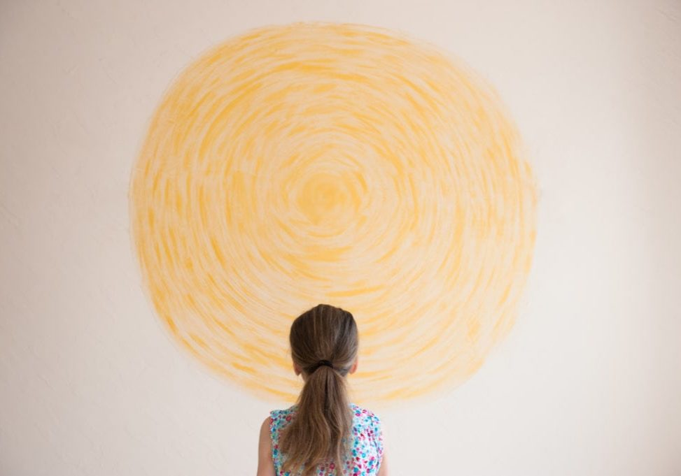 little girl looking at yellow sun painted on wall